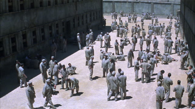 stockvideo's en b-roll-footage met wide angle of prisoners in prison yard. prisoners wear uniforms. men stand talking in groups. some inmates play soccer in bg. correctional facility. state penitentiary. could be used for any 1940's prison in the southwest. - 1940 1949