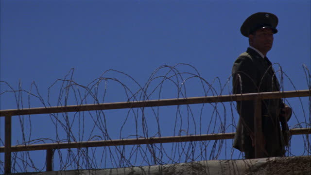 medium angle of prison guards with guns. men walk back and forth on top of guard gate or fence. barbed wire fence rests on wall next to railing. could be used for any 1940's prison in the southwest. weapons. - 1940 1949 stock-videos und b-roll-filmmaterial