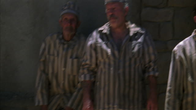 medium angle pan across of prisoners in a prison yard. men wear uniforms. pov. graffiti visible on wall. correctional facility. state penitentiary. could be used for any 1940's prison in the southwest. - 1940 1949 stock-videos und b-roll-filmmaterial