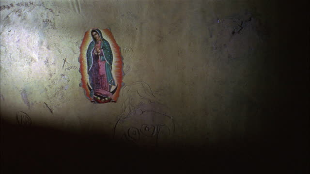 MEDIUM ANGLE OF WALL WITH IMAGE OR ICON OF VIRGIN MARY PRINTED OR PAINTED ON. WALL IS BARE, SCRATCHED, AND MOONLIT. COULD BE USED FOR JAIL CELL OR SIMILAR.