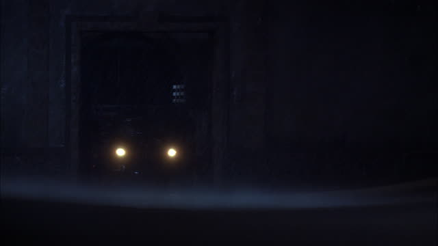 wide angle of truck passing through large gate and wall during storm. gate and wall appear to be guarding a town or a jail or similar. gates opens and truck moves forward. truck is 1940s period with open back. sheets of rain, lightning flashes, and wind v - 1940 1949 stock videos & royalty-free footage