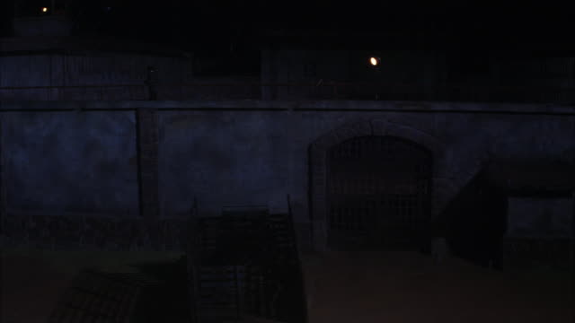 wide angle of jail wall and guard gate. guard walking on top of wall. truck with open back visible in fg. guard lights and jail structure visible in bg. rain, moonlit. - prison wall stock videos & royalty-free footage