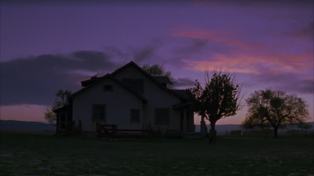 wide angle of a farmhouse or ranch house on a farm or in a rural area of the countryside.  a large tree stands to the side, the sun setting behind it. a light turns on in the window. matching dx/nx 3140-038; 3144-006 to 3144-011; 3144-017 to 3144-019; 314 - ファームハウス点の映像素材/bロール