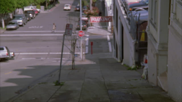 """WIDE ANGLE OF SIDEWALK ALONG  STEEP STREET. """"PARKING"""" SIGN VISIBLE AND ENTRANCE TO PARKING LOT OR PARKING GARAGE. CARS PARKED ON THE SIDE OF THE STREET IN THE BG. VIEW DOWN HILL."""