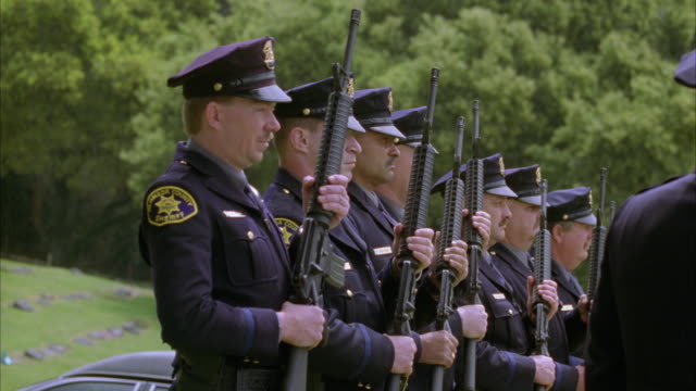 medium angle of row of seven police officers standing a funeral and carrying out 21 gun salute. guns. cemeteries. ceremony. - rifle stock videos & royalty-free footage