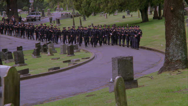 wide angle of police motorcade or funeral procession through a cemetery. police officers march behind police cars with flashing lights and bizbars  followed by fire truck. camera pans right to left and follows  officers. headstones visible. news van in ba - funeral procession stock videos & royalty-free footage