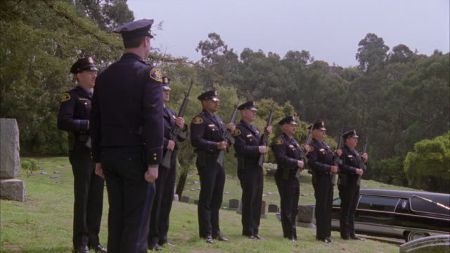 wide angle of police officers carrying out 21 gun salute in cemetery. hearse is in the bg. ceremony. - funeral procession stock videos & royalty-free footage