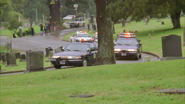 wide angle of police officers in police cars driving slowly through a cemetery as a part of a funeral procession. flashing lights and sirens and bizbars. motorcades. - funeral procession stock videos & royalty-free footage