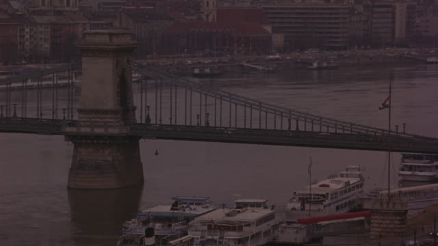 wide angle of the chain bridge over danube river with ferry and tour boats. camera pulls back to capture the full length of bridge. buda castle visible. traffic on roads that run next to river. barges cross under bridge. weather is overcast and foggy. - royal palace of buda stock videos & royalty-free footage