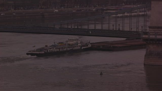 medium angle of ferry boat and barges on danube river under the chain bridge. camera zooms out and  captures the full length of bridge and buda castle visible. traffic on roads that run next to river. weather is overcast and foggy. - royal palace of buda stock videos & royalty-free footage