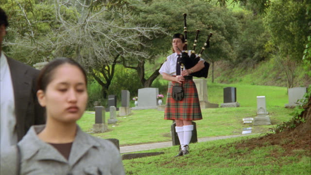 medium angle of bagpiper performing at funeral. mourners are in the fg. ceremony.  cemeteries. musicians. - bagpipes stock videos & royalty-free footage