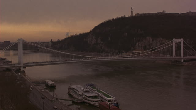 wide angle of the elizabeth bridge over the danube river. ferries are on the river bank as traffic is visible on the road alongside river. buda castle visible. - royal palace of buda stock videos & royalty-free footage
