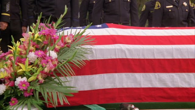 medium angle of coffin or casket covered in american flag. mourners in bg are police officers. flower arrangement at the front of the casket. cemeteries. - funeral stock videos and b-roll footage