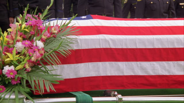 medium angle of coffin or casket covered in american flag. mourners in bg are police officers. flower arrangement at the front of the casket. cemeteries. - coffin stock videos and b-roll footage