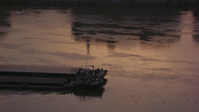 medium angle of barge on danube river. camera zooms out into wide angle of residential or commercial buildings on river bank at sunrise. traffic on road alongside river visible. hills in bg. - river danube video stock e b–roll