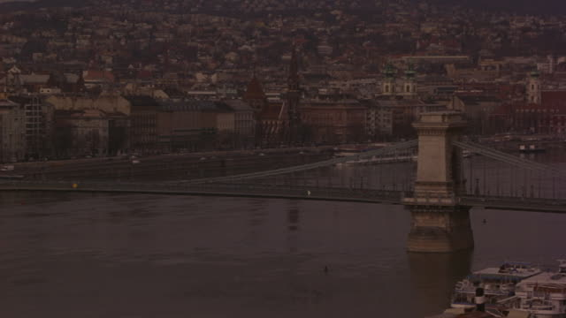 wide angle of the chain bridge over danube river with ferry and tour boats. camera pans up to other river bank. buda castle visible. traffic on  roads that run next to river. weather is overcast and foggy. - royal palace of buda stock videos & royalty-free footage