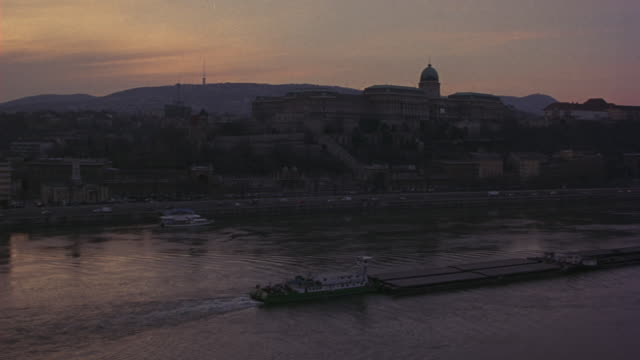 wide angle of buda castle on the riverbank and a barge on the danube river. camera pans right to left down the river captures residential or commercial buildings. traffic on the roads visible. hills in the bg. - royal palace of buda stock videos & royalty-free footage
