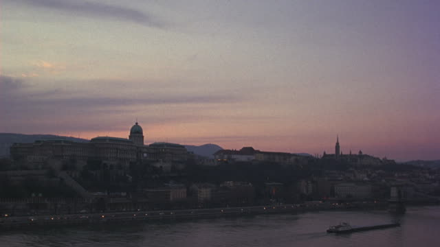 wide angle of sky and clouds at sunrise. camera pans down to capture buda castle and chain bridge on danube river. traffic on road alongside river visible. hills in bg. ferries. - royal palace of buda stock videos & royalty-free footage