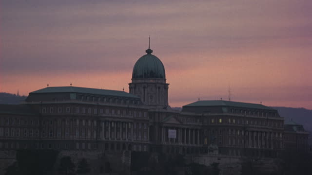 medium angle of buda castle at sunrise as birds fly over. camera pans down to capture the chain bridge on danube river. traffic on road alongside river visible. hills in bg. ferries and barges. - royal palace of buda stock videos & royalty-free footage