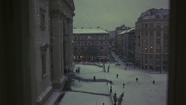 vídeos de stock, filmes e b-roll de wide angle view from window looking down on town or city square. building on left side of frame could be government building such as town hall or library. snow on ground and falling as people walk in and out of building. residential or commercial building - budapest
