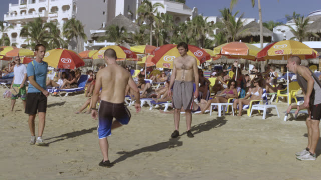 WIDE ANGLE OF MEN ON BEACH PLAYING WITH HACKY SACK. GAMES. BEACH UMBRELLAS. WOMEN AND MEN IN BATHING SUITS. BIKINIS. HOTEL OR RESORT IN BG. PALM TREES IN BG.