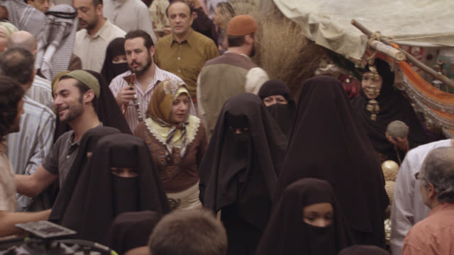 vídeos de stock, filmes e b-roll de medium angle of middle eastern market place. outdoor vendors. men and women. women wear veils or headdresses called hijab. men wear keffiyeh. - adereço de cabeça