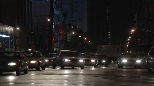 medium angle of traffic on nyc street. cars and taxis. limo swerves through intersection. rain. car stunt. - リムジン点の映像素材/bロール
