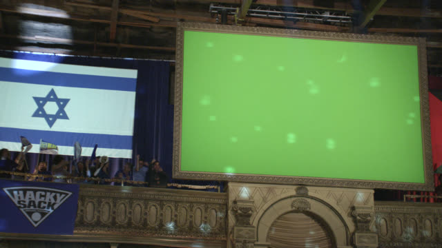 MEDIUM ANGLE OF GREEN SCREEN SCORE BOARD OR INSTANT REPLAY TELEVISION SCREEN. ISRAELI AND PALESTINIAN FLAG. SIGN OR BANNER READS HACKY SACK TOURNAMENT. COULD BE SPORTING EVENT. FLASHING LIGHTS AND SPECTATORS.