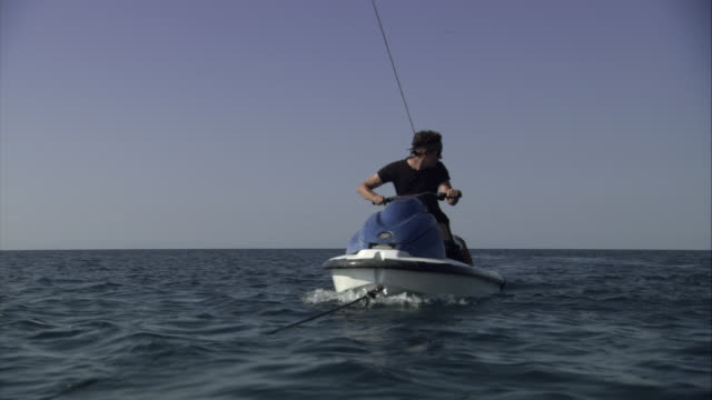 MEDIUM ANGLE OF MAN ON JET SKI IN OCEAN. MAN FLIES OFF INTO WATER. STUNT. ANOTHER JET SKI PICKS MAN UP.