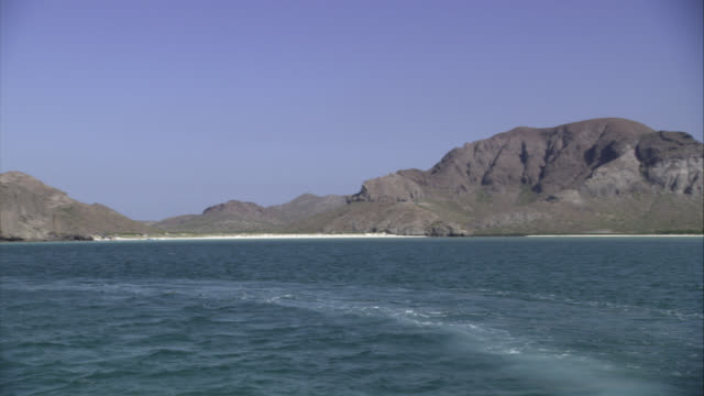 WIDE ANGLE OF COAST AND BEACH IN MEXICO. OCEAN IN FG. COULD BE CLIFFS, BLUFFS, OR MOUNTAINS.