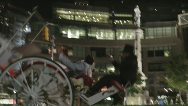 medium angle of bride and groom on horse drawn carriage in new york city. columbus circle in bg. horse bucks backwards and carriage tips over. bride and groom fall to ground. animal stunt.  humorous. weddings. newlyweds. - animal drawn stock videos & royalty-free footage