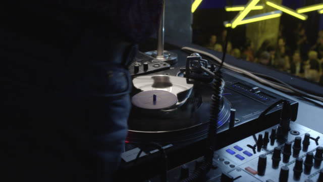close angle of dj in nightclub or bar  spinning records on turn table. high angle down of crowds of people dancing below. neon lights. - bar点の映像素材/bロール