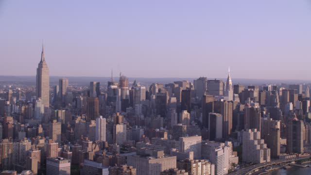 vidéos et rushes de aerial of new york city. high rises, glass office buildings, and apartment buildings visible. city. downtown. skyline. empire state building and chrysler building visible. east river and waterfront visible. citigroup building. - empire state building