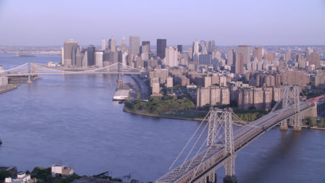 vídeos de stock, filmes e b-roll de aerial of new york city. bridges span between brooklyn and manhattan. high rises, office building, and glass buildings. east river visible. cities and skylines. new york city skyline. brooklyn bridge, manhattan bridge, and williamsburg bridge. - manhattan bridge