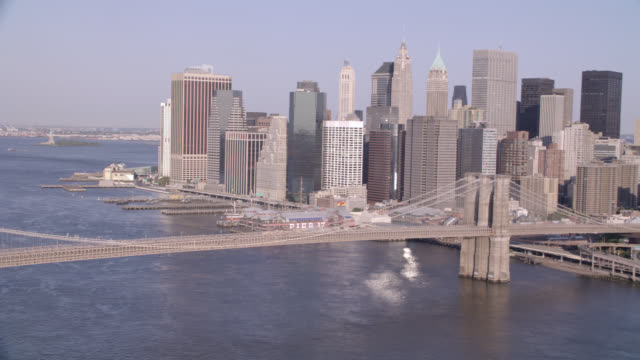 vídeos de stock, filmes e b-roll de aerial of manhattan and brooklyn bridges. east river visible and city skyline in bg. camera pans past brooklyn bridge to statue of liberty in harbor. - manhattan bridge
