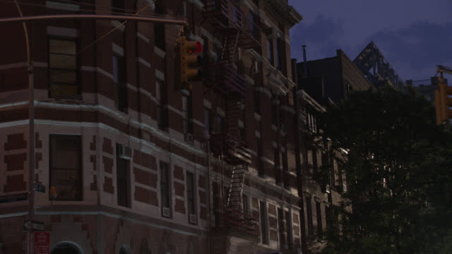 """pan up of multi-story, middle to upper class, brick apartment building in greenwich village. manhattan, at 4th and macdougal. people walking, pedestrians in city street corner. cars and taxis.<p><a href=""""https://www.sonypicturesstockfootage.com/footage?ki - https stock videos & royalty-free footage"""