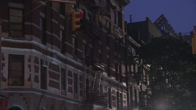 """PAN UP OF MULTI-STORY, MIDDLE TO UPPER CLASS, BRICK APARTMENT BUILDING IN GREENWICH VILLAGE. MANHATTAN, AT 4TH AND MACDOUGAL. PEOPLE WALKING, PEDESTRIANS IN CITY STREET CORNER. CARS AND TAXIS. PEOPLE GET INTO CAB.<P><A HREF=""""HTTPS://WWW.SONYPICTURESSTOCKF"""