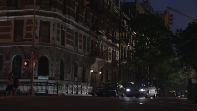 """PAN UP OF MULTI-STORY, MIDDLE TO UPPER CLASS, BRICK APARTMENT BUILDING IN GREENWICH VILLAGE. MANHATTAN, AT 4TH AND MACDOUGAL. PEOPLE WALKING, PEDESTRIANS IN CITY STREET CORNER. CARS AND TAXIS.<P><A HREF=""""HTTPS://WWW.SONYPICTURESSTOCKFOOTAGE.COM/FOOTAGE?KI"""