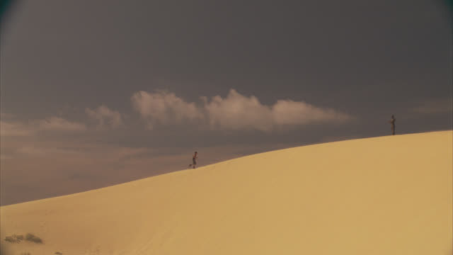 wide angle of man jogging and punching air near statue of man with crossed arms in desert. sand dunes. could be military training. - wide angle stock videos & royalty-free footage