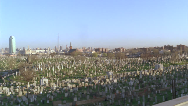 vidéos et rushes de process plate 3/4 right back of cars driving on freeway, expressway, or highway. cemetery or graveyard visible off freeway. skyline in bg. - cimetière