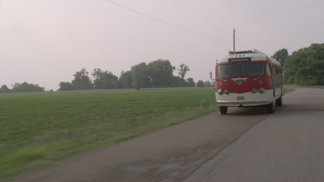 "tracking shot from in front of red passenger 1950 era bus. road in rural area or field in kentucky. bus pulls out of parking area and drives along road. tires and bumper. see ""dewey cox"" in sign above windshield. grove of trees and fields in bg. - ケンタッキー州点の映像素材/bロール"