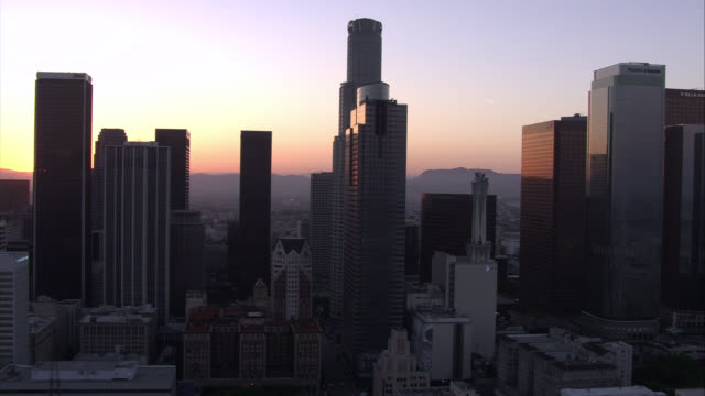 aerial of downtown los angeles at sunset. us bank tower, wells fargo building, gas company tower, paul hastings building, citinational bank, aon, citi, kpmg tower, deloitte and touche, and pacific telephone microwave tower. high rises, skyscrapers, and gl - microwave tower stock videos and b-roll footage