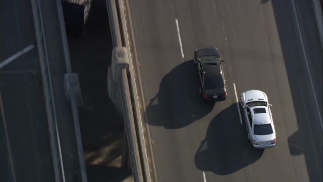 aerial of 101 freeway or highway outside of downtown los angeles. light traffic. camera follow silver mercedes car on freeway. towards pasadena or san gabriel valley and then pans back around to downtown. - pasadena kalifornien stock-videos und b-roll-filmmaterial