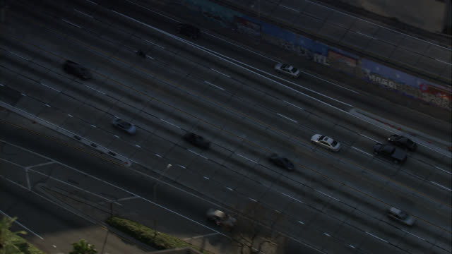 AERIAL OF 110 FREEWAY OR HIGHWAY NEXT TO DOWNTOWN LOS ANGELES. LIGHT TRAFFIC. CAMERA FOLLOW SILVER MERCEDES CAR ON FREEWAY. STAPLES CENTER VISIBLE.