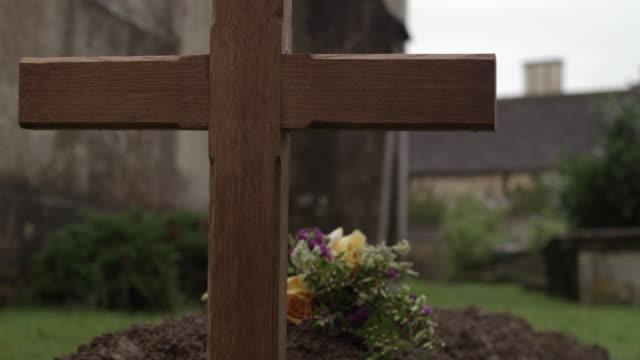 vidéos et rushes de close angle of cross or crucifix marking fresh grave with  bouquets flowers. could be cemetery. stone buildings out of focus in bg. - croix objet de culte