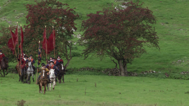 wide angle of renaissance royal guardsmen or entourage of soldiers riding on horses and carrying red flags. could be royal escort, procession or small army of men on horseback. grass, trees, bushes, countrysides. - renaissance stock-videos und b-roll-filmmaterial