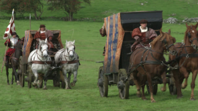 wide angle of renaissance royal guard riding on horses. horse drawn carriages indicate caravan. footmen riding on back of carriage visible. could be royal escort or procession. grass, hillside or meadow. - convoy stock videos and b-roll footage