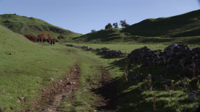 wide angle of renaissance  guards approaching on horseback and holding flags. english countryside. could be royal procession or escort. hills or meadow, rocks visible. blue sky. - royal blue stock videos & royalty-free footage