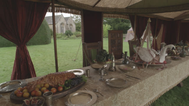 vidéos et rushes de medium angle of royal dining tent set up on yard or grass. wooden tables set with tablecloths and plates. dishes and silverware or utensils. benches at tables. goblets and meat on table. large swan on table.  could be decoration. stone chapel or church in - prendre son repas