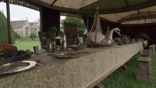 medium angle of royal dining tent set up on yard or grass. wooden tables set with tablecloths and plates. dishes and silverware or utensils. benches at tables. goblets and meat on table. large swan decoration on table.  could be decoration. stone chapel o - swan stock videos & royalty-free footage